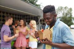 Homme heureux avec le wok et les amis au camion de nourriture Image libre de droits