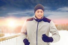 Homme heureux avec les écouteurs et le smartphone en hiver Photos libres de droits