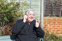 Homme heureux avec son converstation de téléphone portable. Image libre de droits
