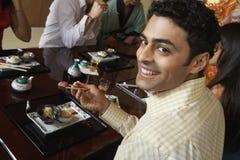 Homme heureux ayant des sushi Photos stock