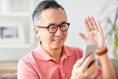 Homme heureux ayant le faire appel visuel au smartphone à la maison Images libres de droits
