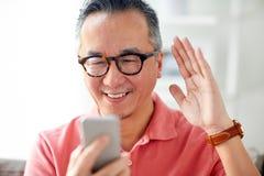 Homme heureux ayant le faire appel visuel au smartphone à la maison Photos libres de droits