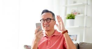 Homme heureux ayant le faire appel visuel au smartphone à la maison Photographie stock libre de droits