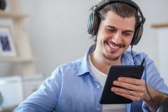 Homme heureux bel regardant au comprimé bleu-foncé Photos stock