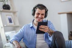 Homme heureux bel regardant au comprimé bleu-foncé Photographie stock