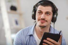Homme heureux bel regardant au comprimé bleu-foncé Images libres de droits