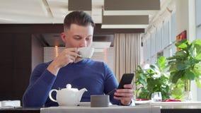 Homme heureux bel riant, utilisant son téléphone intelligent au café pendant le petit déjeuner banque de vidéos