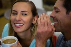 Homme heureux chuchotant dans des oreilles de l'amie ayant le café Images libres de droits