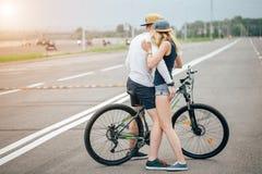 Homme heureux conduisant à amie un sur sa barre transversale de vélo sur la plage Photos stock