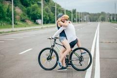 Homme heureux conduisant à amie un sur sa barre transversale de vélo sur la plage Image libre de droits