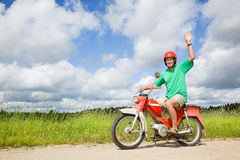 Homme heureux conduisant un vélomoteur Images stock