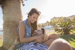 Homme heureux détendant dehors avec l'amie la regardant Images stock