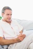 Homme heureux détendant sur son divan utilisant le PC de comprimé Image stock