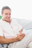Homme heureux détendant sur son divan utilisant le PC de comprimé regardant le camer Images libres de droits
