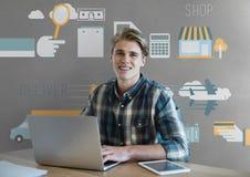 Homme heureux d'affaires à un bureau utilisant un ordinateur sur le fond gris avec des graphiques Photos stock
