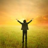 Homme heureux d'affaires dans les domaines et le coucher du soleil verts Photographie stock