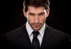 Homme heureux d'affaires de brune caucasienne dirigeant la main d'isolement sur le noir Photos stock