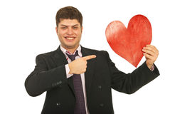 Homme heureux d'affaires indiquant le coeur Photographie stock libre de droits