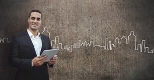 Homme heureux d'affaires tenant un comprimé sur le fond gris de mur avec des icônes de ville Photos stock