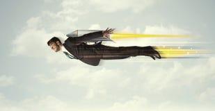 Homme heureux d'affaires volant rapidement sur le ciel entre les nuages Image libre de droits