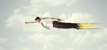 Homme heureux d'affaires volant rapidement sur le ciel entre les nuages Photo libre de droits