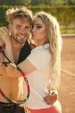 Homme heureux d'amant d'étreinte de femme sur le court de tennis Image stock