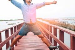 Homme heureux dans des jeans occasionnels sur le pont en bois Image libre de droits