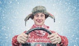 Homme heureux dans le chandail et le chapeau rouges avec un volant, tempête de neige de neige Conducteur de voiture de concept photographie stock