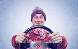 Homme heureux dans le chandail et le chapeau avec un volant, tempête de neige de neige Conducteur de voiture de concept photos libres de droits