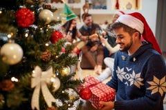Homme heureux dans le chapeau du ` s de Santa avec des cadeaux de Noël à la maison Photo stock