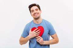 Homme heureux dans le T-shirt étreignant le coeur de papier Images libres de droits
