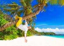Homme heureux dans les pantalons jaunes et la chemise blanche accrochant sur une paume t Photo stock