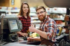 Homme heureux de caissier sur l'espace de travail dans le supermarché Photos libres de droits