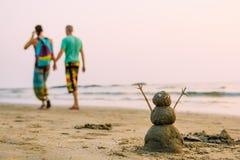 Homme heureux de Sandy sur la plage de mer contre la marche de couples des hommes photographie stock