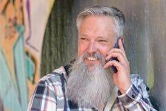 Homme heureux de sourire causant sur son mobile Image libre de droits