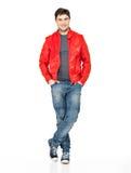 Homme heureux de sourire dans la jupe, les blues-jean et les gymshoes rouges. Image libre de droits