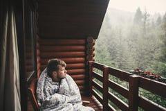 Homme heureux de voyageur se reposant dans la couverture sur le porche en bois avec la vue sur des bois et des montagnes L'espace photographie stock