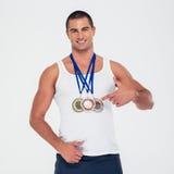 Homme heureux dirigeant le doigt à ses médailles d'or photographie stock libre de droits