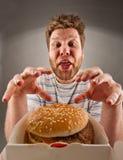 Homme heureux disposant à manger l'hamburger photographie stock libre de droits