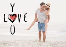 Homme heureux donnant le ferroutage de femme sur la plage Photos libres de droits
