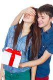 Homme heureux donnant un cadeau à son amie Jeunes beaux couples heureux d'isolement sur un fond blanc Photographie stock libre de droits