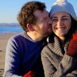 Homme heureux embrassant l'amie devant la plage en hiver Image libre de droits