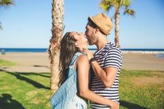 Homme heureux embrassant son amie souriant dehors Image libre de droits