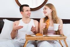 Homme heureux et belle amie avec le petit déjeuner savoureux Photographie stock libre de droits