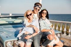 Homme heureux et deux femmes se tenant ensemble près du cabriolet de vintage Photos stock