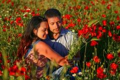 Homme heureux et femme étreignant dans un domaine des pavots photos stock