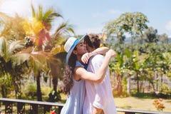 Homme heureux et femme étreignant sur la terrasse ou le balcon avec de jeunes couples de beau paysage tropical dans l'étreinte bl Images libres de droits