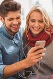 Homme heureux et femme ayant l'amusement avec le téléphone Photos libres de droits