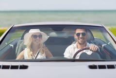 Homme heureux et femme conduisant dans la voiture de cabriolet Photo stock