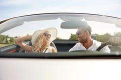 Homme heureux et femme conduisant dans la voiture de cabriolet photos stock